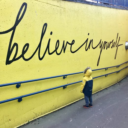 toddler looking at believe in yourself graffiti