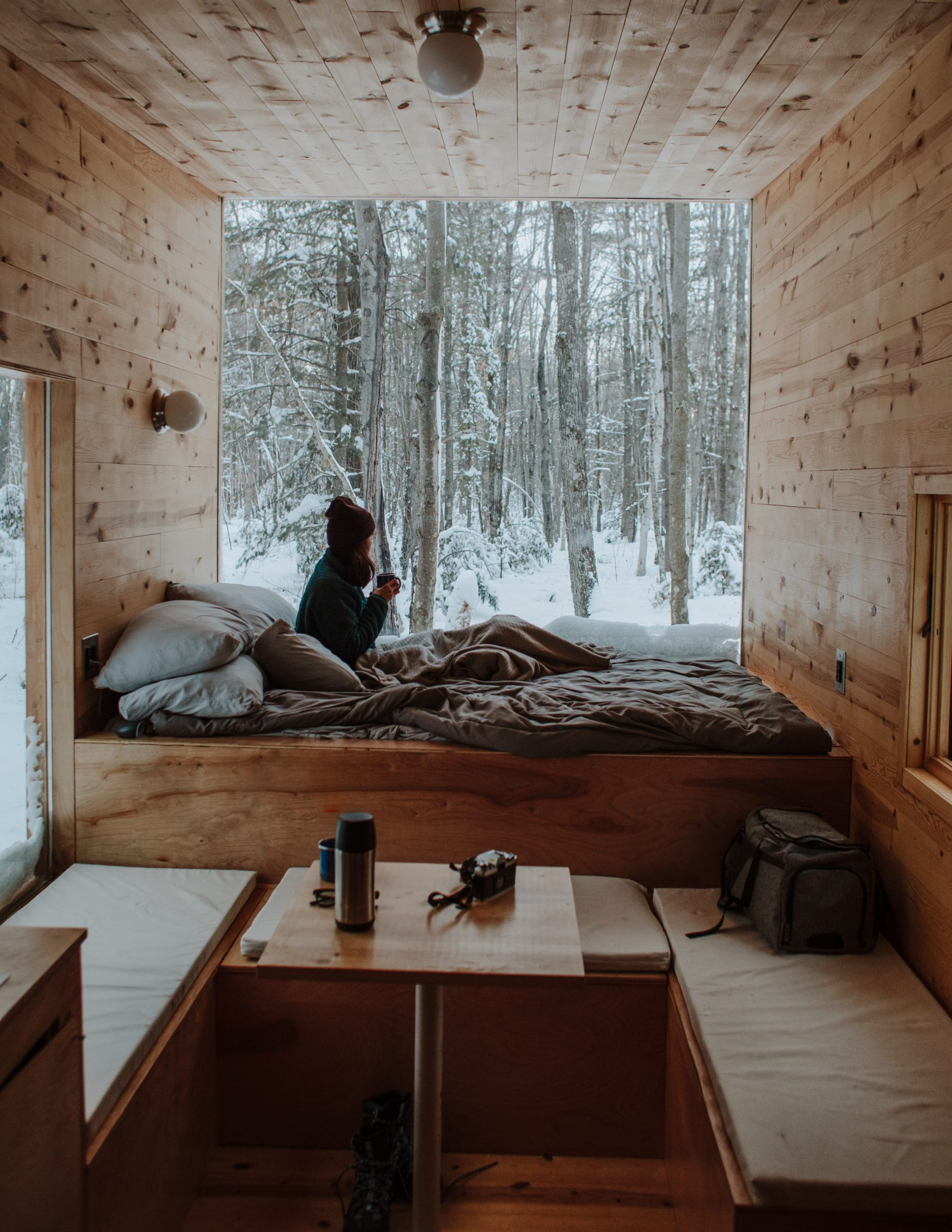 woman sitting on bed watching by the window during winter