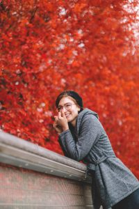 woman in gray sweater sitting on brown wooden bench