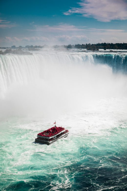 red boat on water falls during daytime