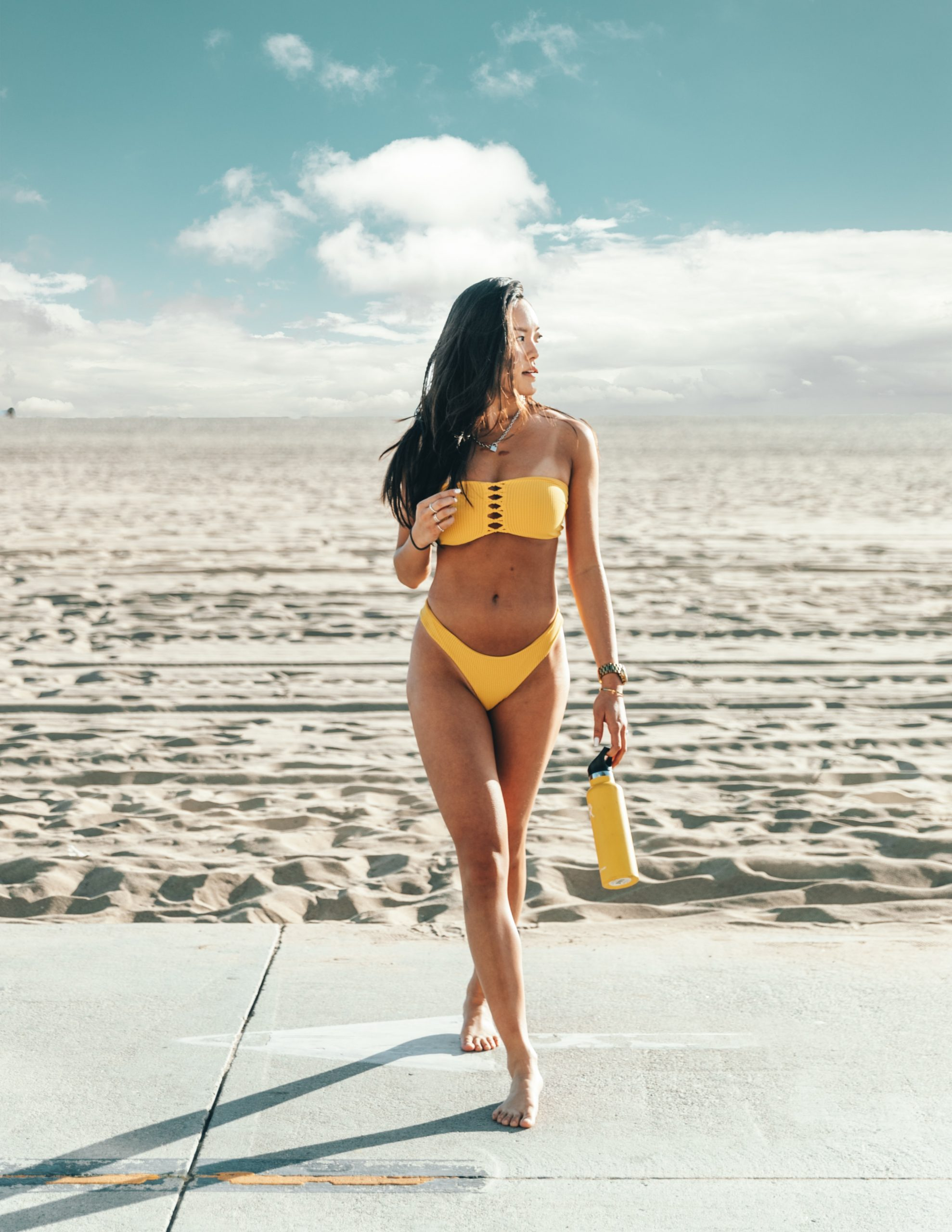 standing woman wearing yellow bikini holding yellow bottle